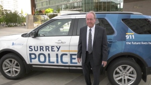 Surrey Mayor Doug McCallum stands in front of a police car.