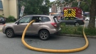 Firefighters smashed the windows of this vehicle and ran their hose right through it in order to access a fire hydrant while battling a blaze in Halifax on July 22, 2019. (CTV / JIM KVAMMEN)