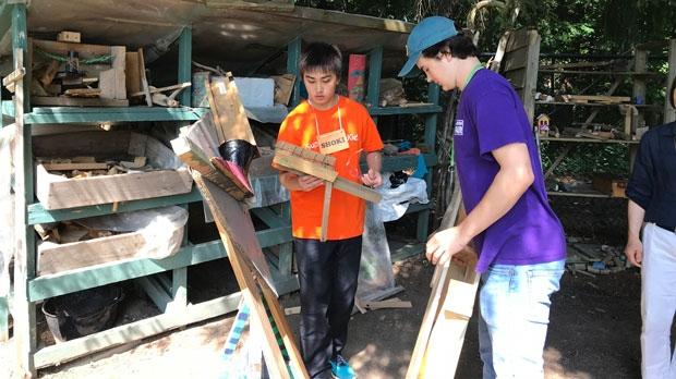 Shoki, a student visiting from Japan, learns about woodworking at Holland Bloorview's Spiral Garden. (Pauline Chan/CTV News Toronto)