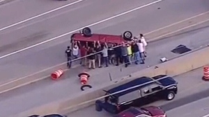 Bystanders work together to right flipped truck