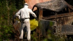 A forensics expert is seen working on a burned truck near Dease Lake, B.C. on July 23, 2019.