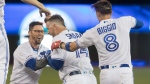 Toronto Blue Jays' Justin Smoak celebrates with teammates Eric Sogard and catcher Cavan Biggio after he hit a walk off single in the tenth inning to defeat the Cleveland Indians in their American League MLB baseball game in Toronto Tuesday July 23, 2019. THE CANADIAN PRESS/Fred Thornhill