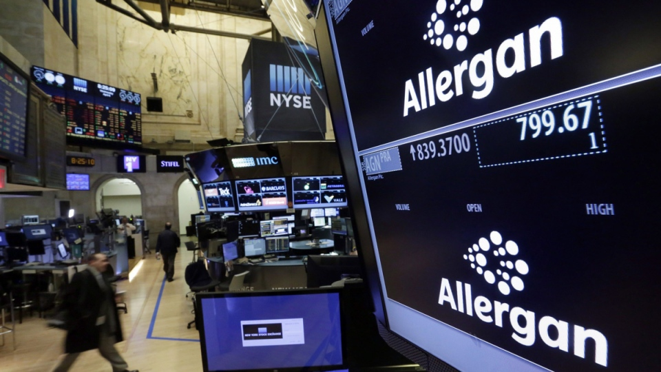 Allergan logos appear on screens above its trading post on the floor of the New York Stock Exchange, on April 6, 2016. (Richard Drew / THE CANADIAN PRESS / AP)