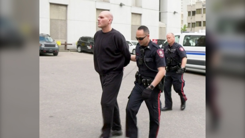 Barry Roach, 48, is led into the Arrest Processing Unit by Calgary Police Service members in June 2019. Roach was charged with second-degree murder in connection with the death of Jeremy Boisseau.