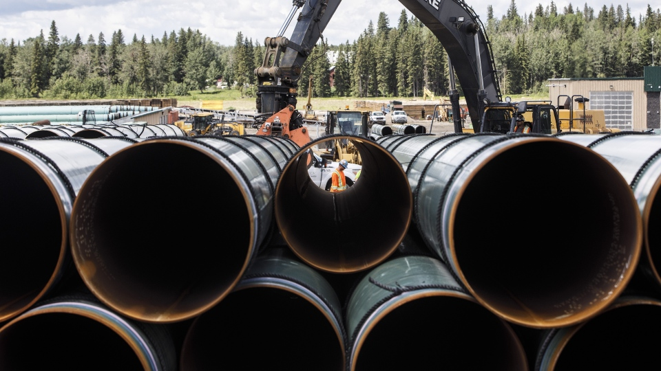 Pipe for the Trans Mountain pipeline are unloaded in Edson, Alta. on June 18, 2019. THE CANADIAN PRESS/Jason Franson