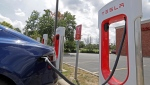 In this July 19, 2019, photo a Tesla vehicle charges at a Tesla Supercharger site in Charlotte, N.C. (AP Photo/Chuck Burton)