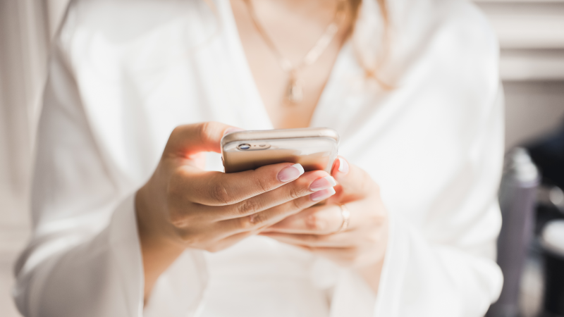 A woman uses a smartphone in an image from shutterstock.com