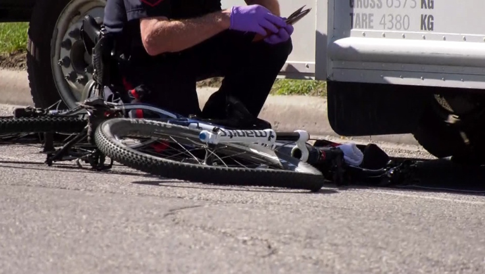 A CPS member kneels next to a damaged bicycle following Friday afternoon's crash in a northeast industrial area