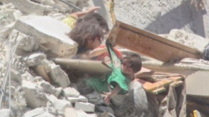 This close-up of the image shows the infant dangling from her sister's hand, as the two older sisters struggle under the rubble. (Bashar al-Sheikh / SY24)