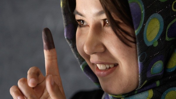 An Afghan woman shows the dye on her finger after casting her ballot at a polling station in a school in Kabul, Thursday, Aug. 20, 2009. (AP / Kevin Frayer)