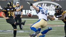 Hamilton Tiger-Cats kicker Lirim Hajrullahu (70) punts during second half CFL football game action against the Winnipeg Blue Bombers in Hamilton, Ont. on Friday, July 26, 2019. (THE CANADIAN PRESS/Peter Power)