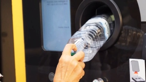 A traveler places a plastic bottle into one of the new recycling machines. (CTV NEWS LONDON)