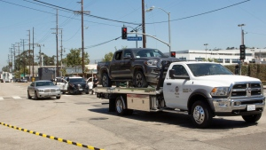 Police officers tow a truck during an investigation into the killing of a fellow officer in the Lincoln Heights area of Los Angeles on Saturday, July 27, 2019. Authorities said off-duty Officer Juan Diaz was out with his girlfriend when he was shot and killed at a taco stand early Saturday. Another man was hospitalized from the shooting. Chief Michel Moore has asked for the public's help in finding the attacker. (AP Photo/Damian Dovarganes)