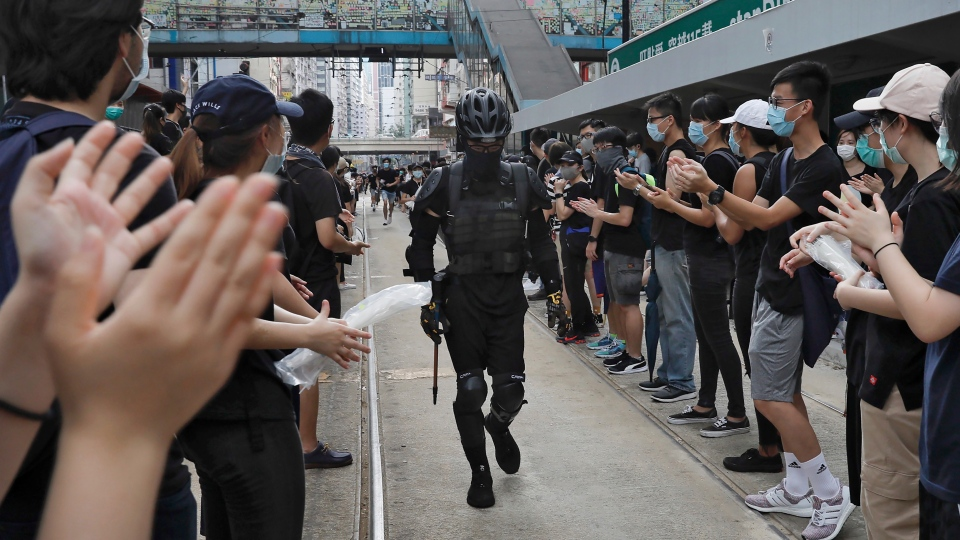 Protesters cheer a colleague wearing a full protection gear as they take part in a march on a street in Hong Kong, Sunday, July 28, 2019. A sea of black-shirted protesters, some with bright yellow helmets and masks but many with just backpacks, marched down a major street in central Hong Kong on Sunday in the latest rally in what has become a summer of protest. (AP Photo/Vincent Yu)