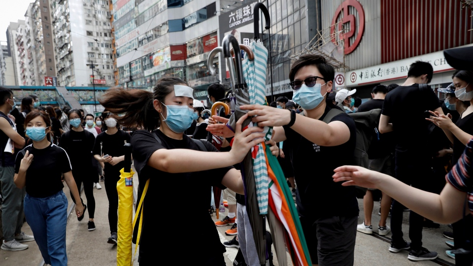Protesters distribute umbrellas to take part in a march on a street in Hong Kong, Sunday, July 28, 2019. (AP Photo/Vincent Yu)