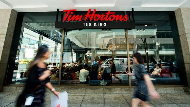 People walk past the newly renovated Tim Hortons in Toronto on Thursday, July 25, 2019. (THE CANADIAN PRESS / Nathan Denette)