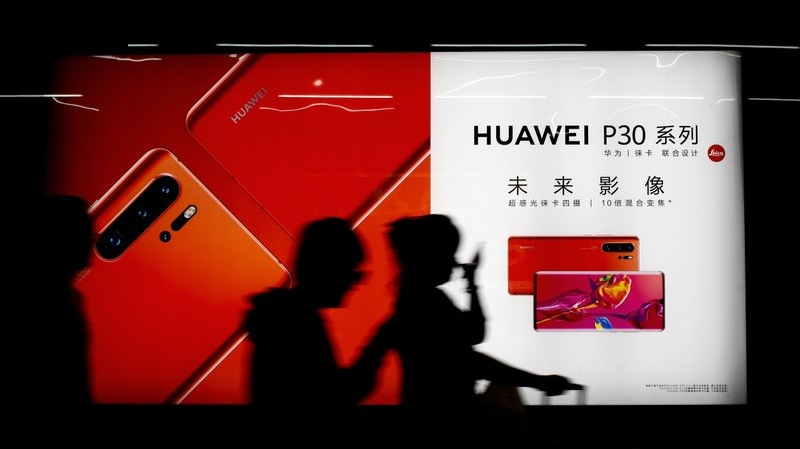 FILE - In this May 13, 2019, file photo, commuters walk by the new Huawei P30 smartphone advertisement on display inside a subway station in Beijing. (AP Photo/Andy Wong, File)