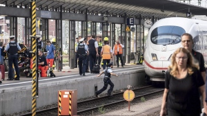 Firefighters and Police officers stay next to an ICE highspeed train at the main station in Frankfurt, Germany, July 29, 2019.  (Frank Rumpenhorst / dpa via AP)