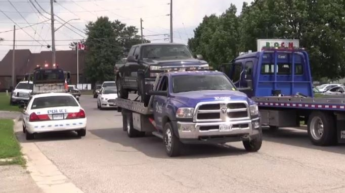 A pickup truck is towed after a police search of a business in east London, Ont. on Monday, July 29, 2019. (Gerry Dewan / CTV London)