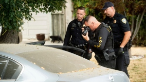 A police officer photographs a car outside the family home of Gilroy Garlic Festival gunman Santino William Legan on Monday, July, 29, 2019, in Gilroy, Calif. (AP Photo/Noah Berger)