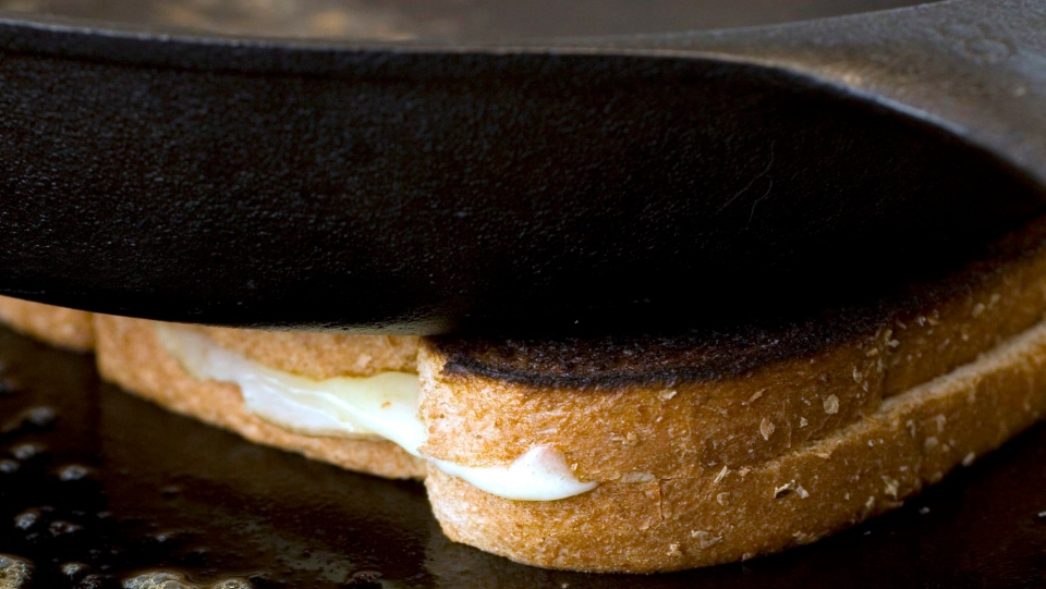 A cast iron pan is used to weigh down a grilled cheese sandwich as it cooks on a skillet on July 31, 2007. (THE CANADIAN PRESS/AP, Larry Crowe)