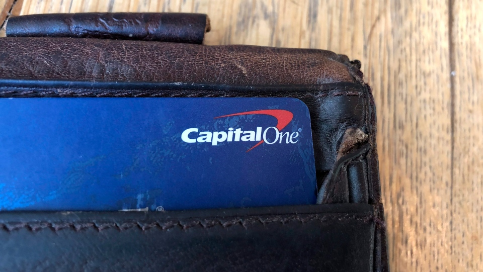 In this Tuesday, July 16, 2019, photo a Capital One credit card is shown in a man's wallet in San Francisco. (AP Photo/Jeff Chiu)