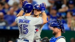 Toronto Blue Jays right fielder Randal Grichuk (15) celebrates his two-run home run with teammate Cavan Biggio, back, during the sixth inning of a baseball game at Kauffman Stadium in Kansas City, Mo., Monday, July 29, 2019. Kansas City Royals catcher Cam Gallagher, right, waits at home plate. (AP Photo/Orlin Wagner)