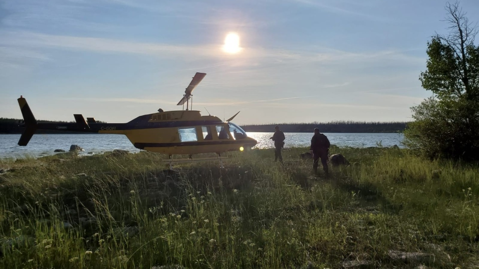 Officers look through a remote lake area alongside a landed helicopter in the Gillam, Man., area in July 28, 2019, police image published to social media. THE CANADIAN PRESS/HO-Twitter, Royal Canadian Mounted Police, @rcmpmb