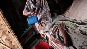 In this Friday, Nov. 14, 2014, file photo, Nurunnahar pours water on the forehead of her father-in-law Mohammad Habib, 90, to bring down a fever, at his home in the highly polluted Hazaribagh tannery area in Dhaka, Bangladesh. (AP Photo/A.M. Ahad, file)