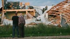 Residents look over a destroyed printing facility by damage caused when an apparent tornado touched down on the edge of Durham, Ontario, Thursday, August 20, 2009. (Dave Chidley / THE CANADIAN PRESS)