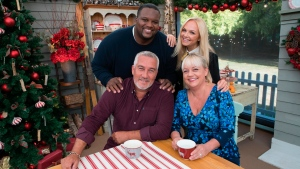 """This image released by ABC shows Anthony Adams, standing left, Emma Bunton, standing right, Paul Hollywood, seated left, and Sherry Yard from the competitive baking series, """"The Great American Baking Show: Holiday Edition."""" (ABC via AP)"""