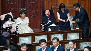 Two newly-elected lawmakers, Yasuhiko Funago, third from right, and Eiko Kimura, left, in wheelchairs are helped to vote during an extraordinary session of the parliament's upper house in Tokyo Thursday, Aug. 1, 2019. (Muneyuki Tomari/Kyodo News via AP)