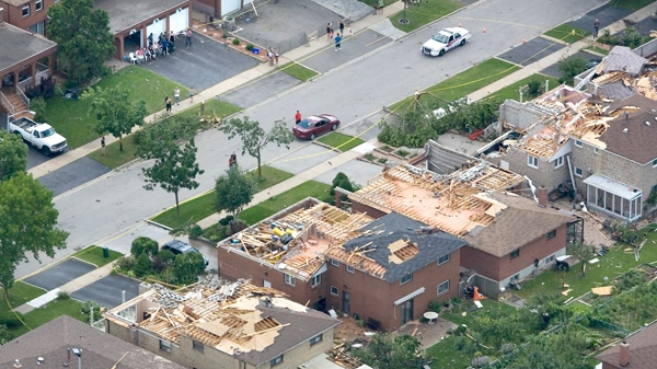 Residents gather in front of damaged homes in Vaughan, Ont., on Friday, August 21, 2009. (Darren Calabrese / THE CANADIAN PRESS)