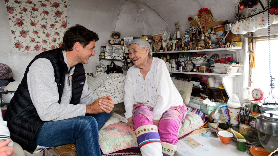Prime Minister Justin Trudeau talks with Inuit elder Qaapik Attagutsiak, 99, in her tiny home during a visit to Arctic Bay, Nvt., on Thursday, Aug. 1, 2019.THE CANADIAN PRESS/Sean Kilpatrick