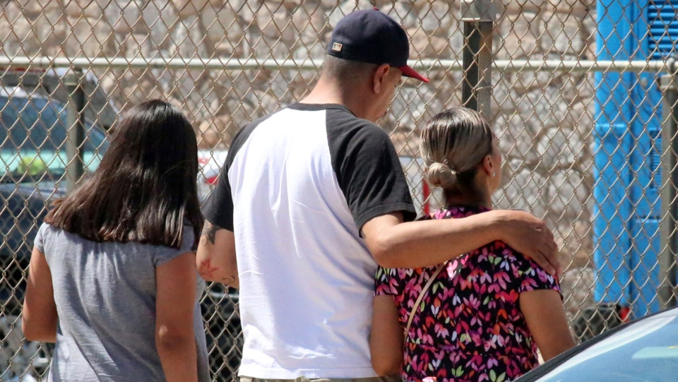 People walk out of an elementary school after family members were asked to reunite following a shooting at a shopping mall in El Paso, Texas, on Saturday, Aug. 3, 2019. (AP Photo/Rudy Gutierrez)