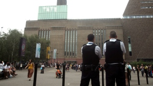 "Emergency crews attending a scene at the Tate Modern art gallery, London, Sunday, Aug. 4, 2019. London police say a teenager was arrested after a child ""fell from height"" at the Tate Modern art gallery. (Yui Mok/PA via AP)"