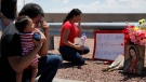 Dr. Julio Novoa, left, and Danielle Novoa, right, kneel beside a makeshift memorial with their 10-month-old son Ricard Novoa at the scene of a mass shooting at a shopping complex Sunday, Aug. 4, 2019, in El Paso, Texas. (AP / John Locher)