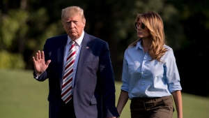 U.S. President Donald Trump waves to members of the media as he and first lady Melania Trump walk across the South Lawn of the White House in Washington, Sunday, Aug. 4, 2019, as they return from Bedminster, N.J. (AP Photo/Andrew Harnik)