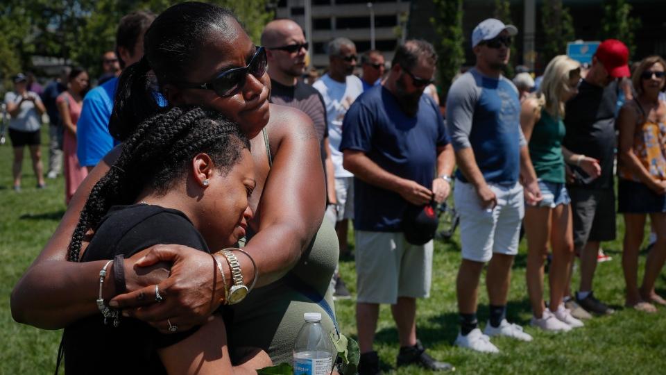Mourners gather at a vigil following a nearby mass shooting, Sunday, Aug. 4, 2019, in Dayton, Ohio. (AP Photo/John Minchillo)