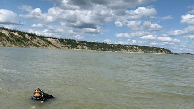 The dive team was called in after RCMP officers searching from a helicopter located a damaged aluminum boat on the shores of the Nelson River Friday. (Photo: RCMP/Twitter)