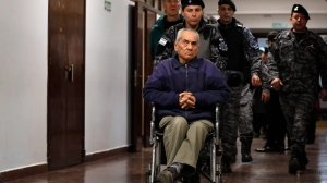 Rev. Nicola Corradi, centre, and Rev. Horacio Corbacho, following behind on left, are escorted from the courtroom after attending their trial in Mendoza, Argentina, Monday, Aug. 5, 2019.  (AP Photo/Natacha Pisarenko)
