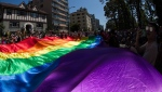 A large rainbow flag is carried by people marching in the Vancouver Pride Parade, in Vancouver, Sunday, Aug. 4, 2019. THE CANADIAN PRESS/Darryl Dyck