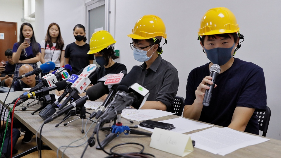 Protesters from right, Jerry Chan, Linus Kim and Mary Tsang attend a press conference in Hong Kong, Tuesday, Aug. 6, 2019. (AP Photo/Kin Cheung)