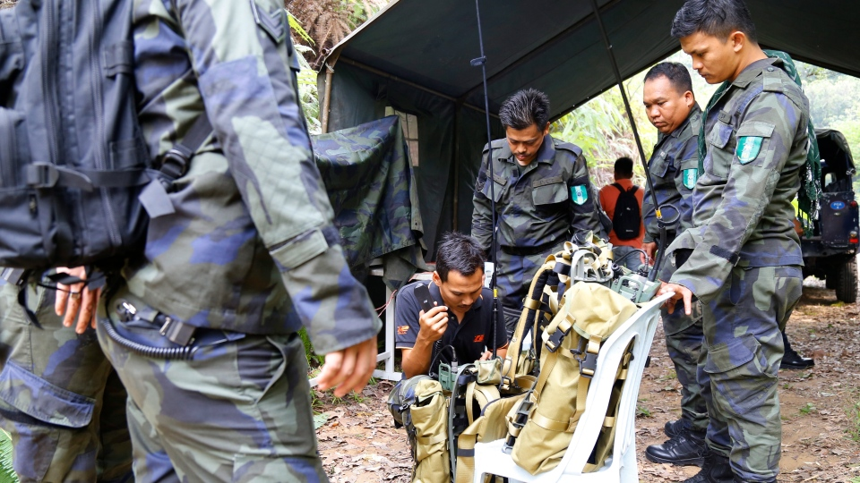 Members of General Operations Force work at a temporary operation shelter near The Dusun resort where a 15-year-old London girl went missing, in Seremban, Negeri Sembilan, Malaysia, Tuesday, Aug. 6, 2019. (AP Photo/Lai Seng Sin)