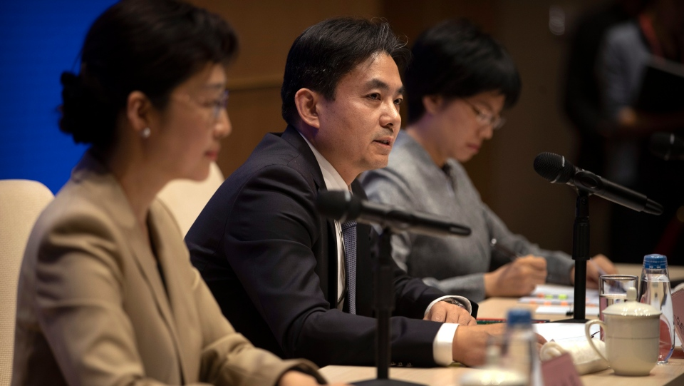 Yang Guang, center, spokesman for the Chinese Cabinet's Hong Kong and Macao Affairs Office, speaks during a press conference in Beijing, Tuesday, Aug. 6, 2019. (AP Photo/Mark Schiefelbein)