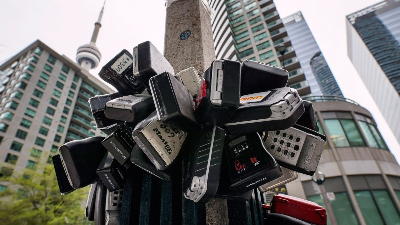 Lockboxes, typically used by real estate agents to store keys for apartment and condominium showings, are seen attached to a street lamp outside an area of condo buildings in downtown Toronto, Friday May 12, 2017. THE CANADIAN PRESS/Mark Blinch