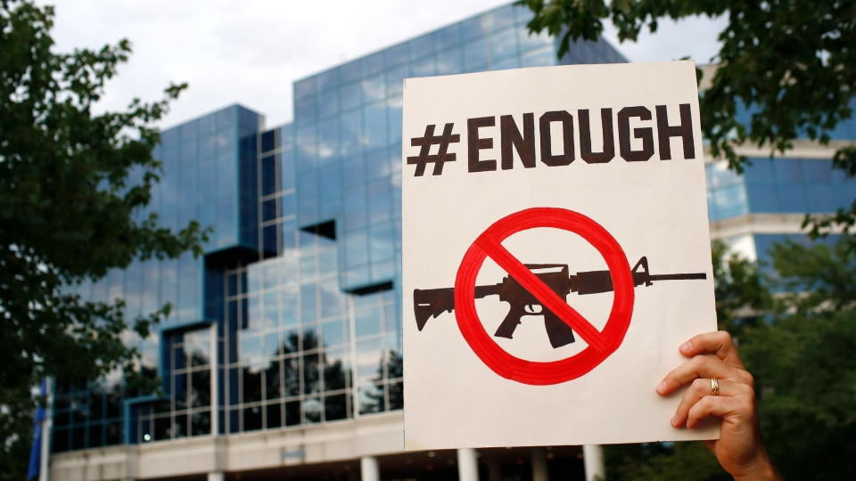 Protester Matt McCabe holds a sign outside the National Rifle Association's headquarters building during a vigil for recent victims of gun violence, Monday, Aug. 5, 2019, in Fairfax, Va. (AP Photo/Patrick Semansky)