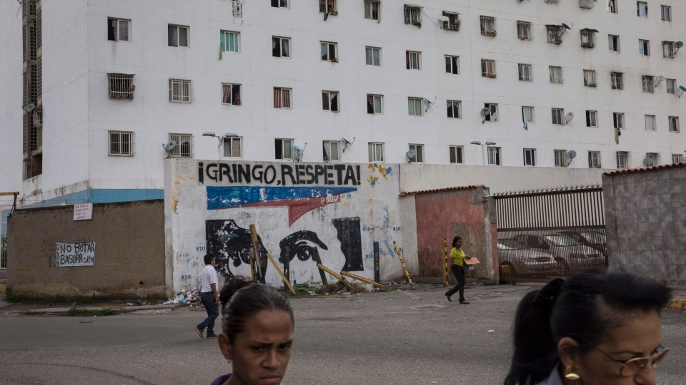 """People walk next to graffiti with the image of Venezuelan Independence hero Simon Bolivar and a phrase that reads in Spanish """"Gringo, respect us"""" in Caracas, Venezuela, Tuesday, July 16, 2019. (AP Photo/Rodrigo Abd)"""