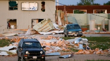 Missing walls, broken windows and debris fill a street damaged when an apparent tornado touched down on the edge of Durham, Ontario, Thursday, August 20, 2009. (Dave Chidley / THE CANADIAN PRESS)