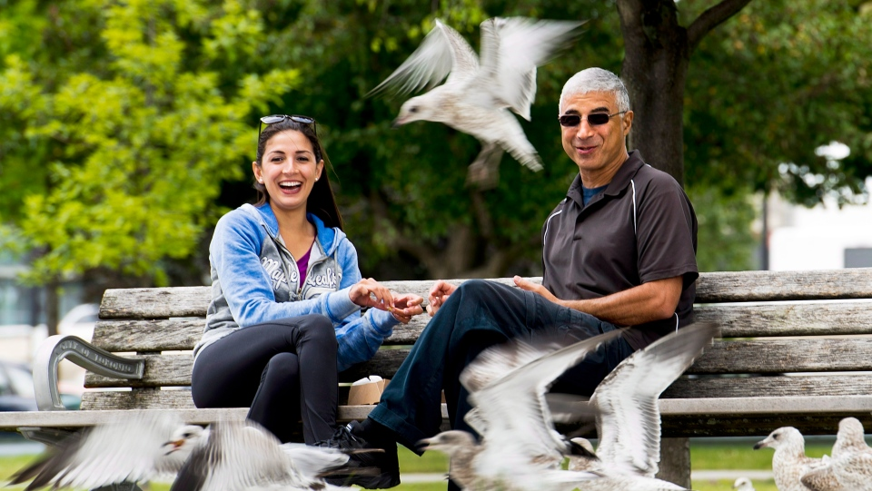 Ashley Cate, left, and her father Adam Cate, right, feed seagulls on the boardwalk along Lake Ontario in Toronto. on Tuesday, July 29, 2014. THE CANADIAN PRESS/Nathan Denette